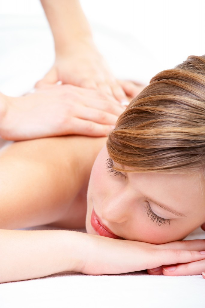 Young woman lying on massage table at spa, eyes closed.